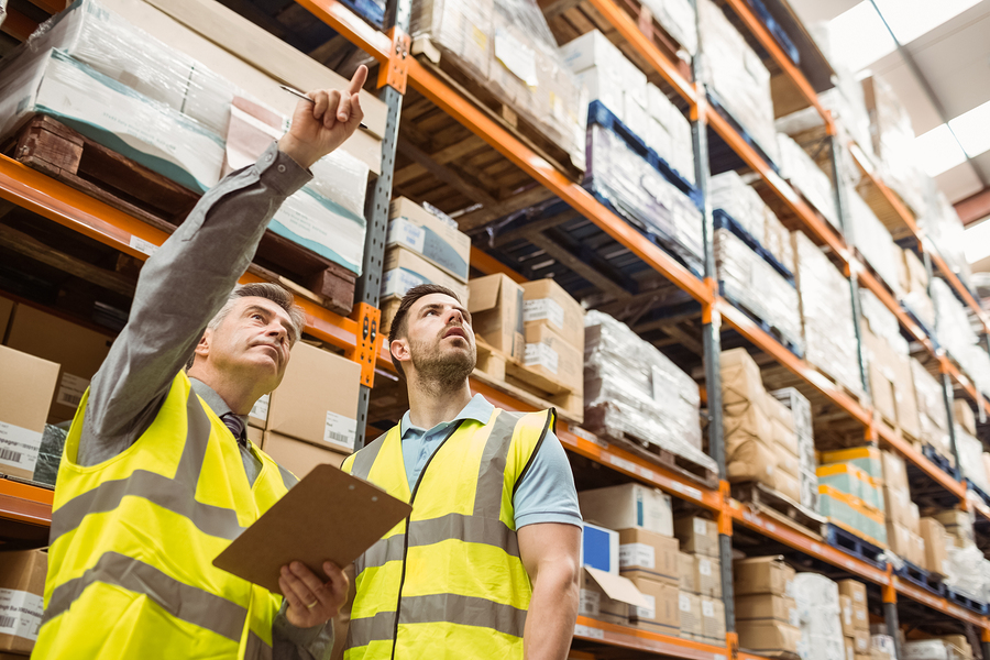 Warehouse manager and foreman working together in a large wareho